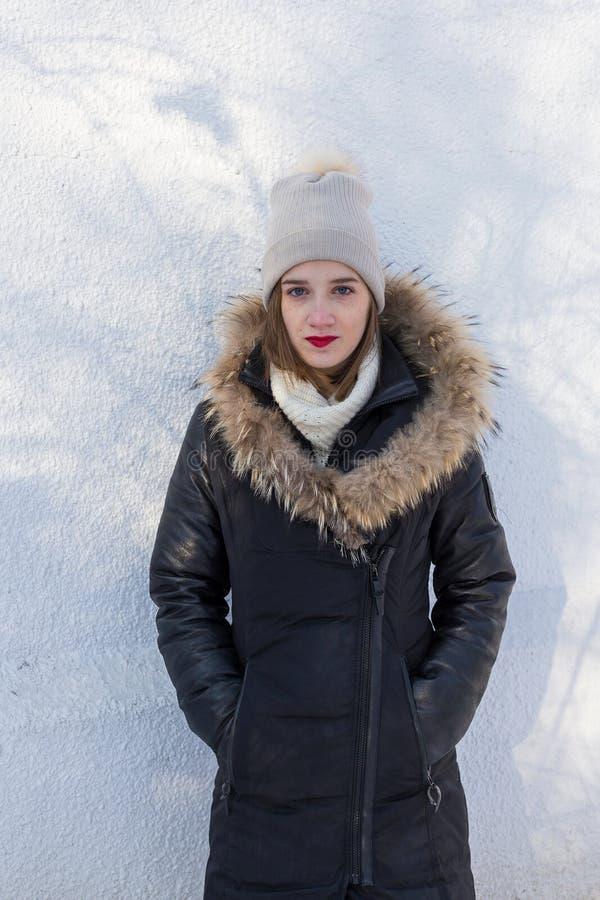 Młoda dziewczyna jest ubranym żyłującego żakiet przeciw białej stiuk ścianie zdjęcie royalty free