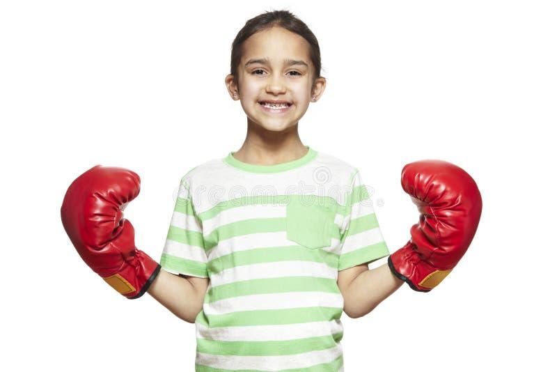 Młoda dziewczyna jest ubranym bokserskich rękawiczek ono uśmiecha się zdjęcie stock