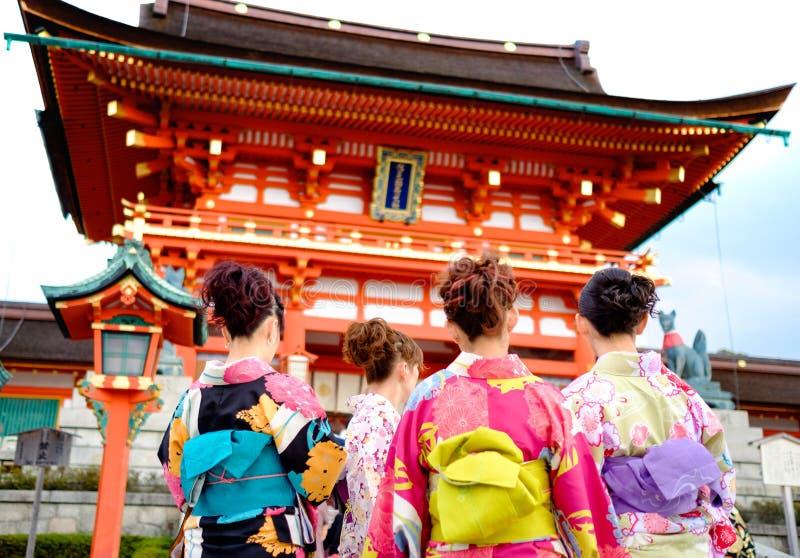 Młoda dziewczyna jest ubranym Japońską kimonową pozycję przed japończykiem obrazy stock