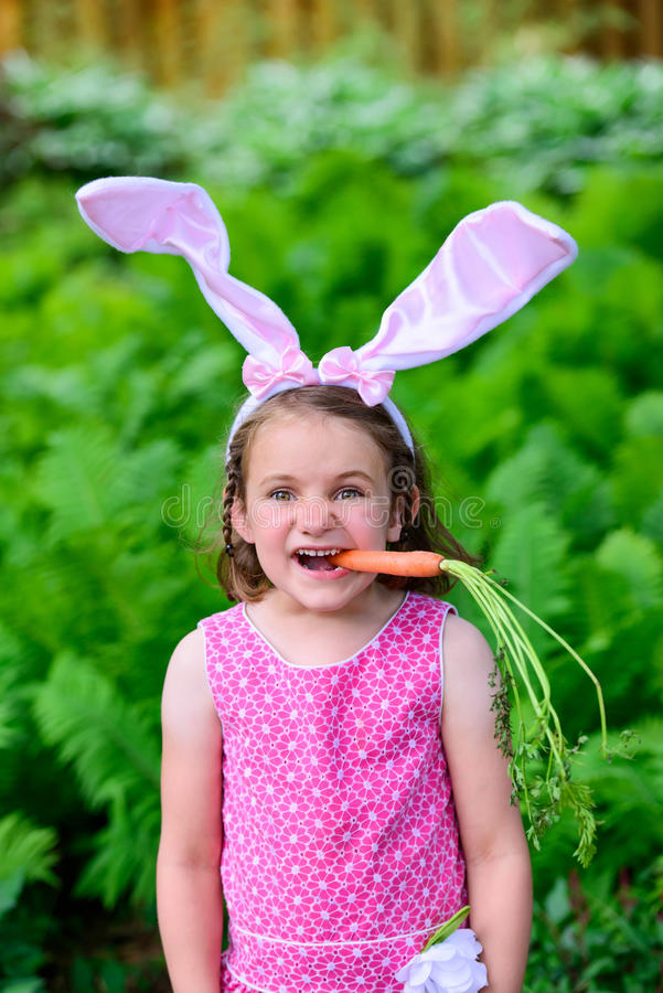 Młoda Dziewczyna Jest ubranym królików ucho z marchewką w Jej usta fotografia royalty free