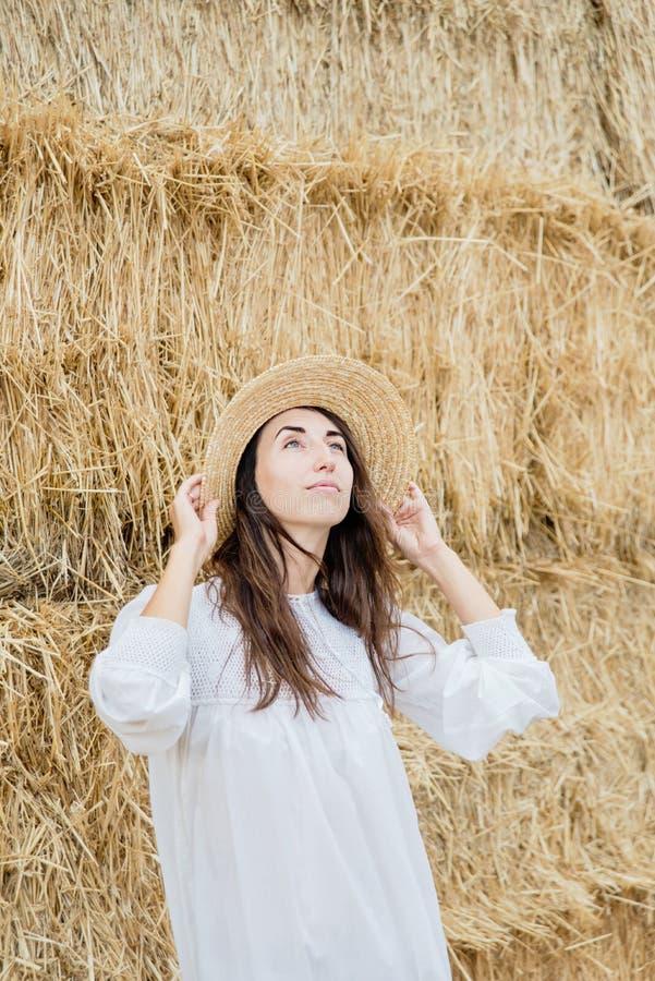 Młoda dziewczyna jest ubranym lato bielu suknię blisko siano beli w polu Piękna dziewczyna na rolnej ziemi Pszeniczny żółty złoty zdjęcie stock