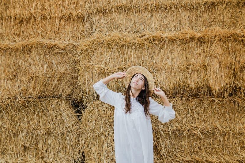 Młoda dziewczyna jest ubranym lato bielu suknię blisko siano beli w polu Piękna dziewczyna na rolnej ziemi Pszeniczny żółty złoty obrazy stock