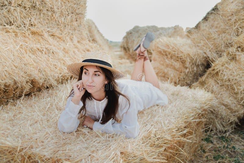 Młoda dziewczyna jest ubranym lato bielu suknię blisko siano beli w polu Piękna dziewczyna na rolnej ziemi Pszeniczny żółty złoty zdjęcie royalty free