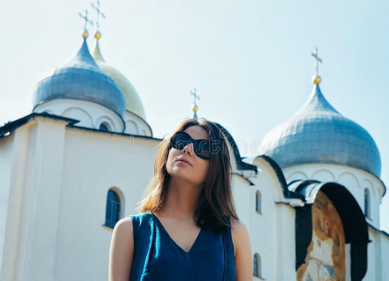 Młoda dziewczyna jest ubranym okulary przeciwsłoneczni katedrę St Sophia w Kremlin Veliky Novgorod Rosja zdjęcia stock