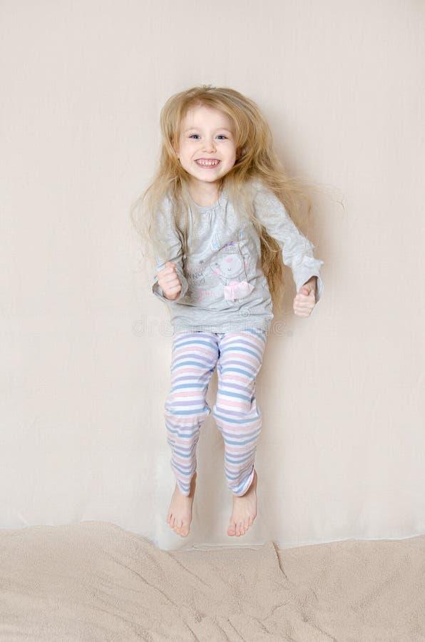 Młoda Dziewczyna Jest ubranym piżam Skakać obrazy stock