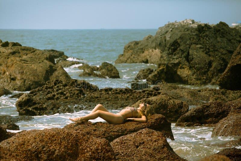 Młoda dziewczyna kłama na kamieniach na plaży w bikini z pięknym ciałem i okularami przeciwsłonecznymi fotografia royalty free