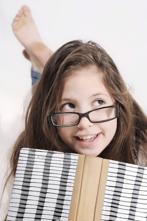 Młoda dziewczyna kłama na podłoga z książką fotografia stock