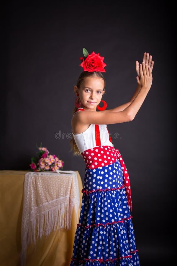 Młoda dziewczyna klascze ręki w flamenco stroju zdjęcia stock