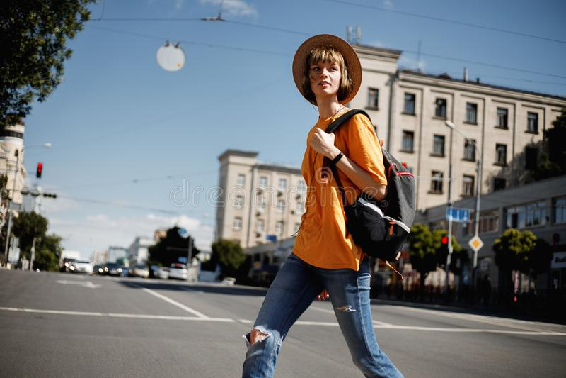 Młoda dziewczyna krzyżuje drogę z plecakiem w miasto ulicie na a z hełmofonami w żółtej koszulce i słomianym kapeluszu fotografia stock