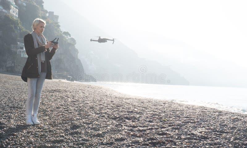 Młoda dziewczyna latający truteń nad włocha wybrzeżem fotografia stock
