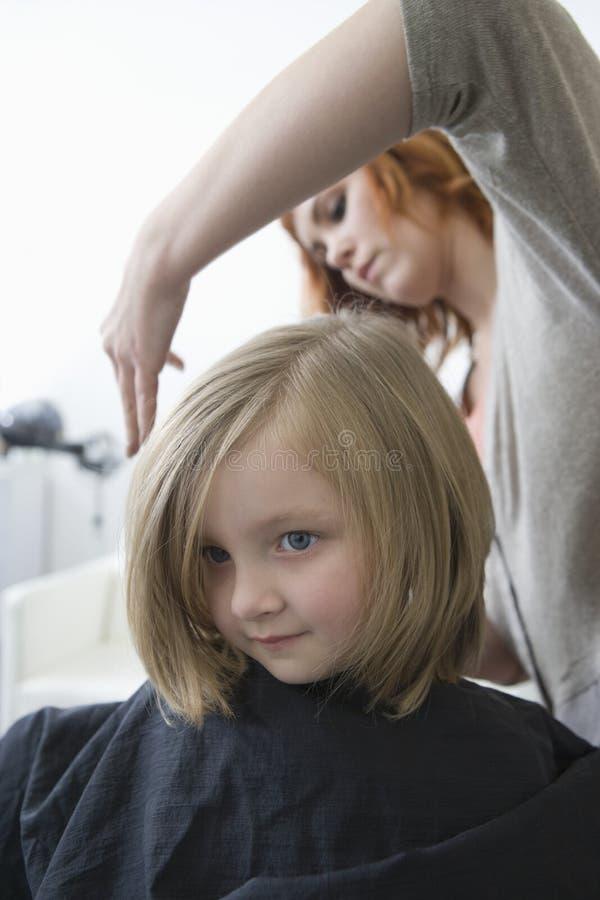 Młoda dziewczyna ma jej włosy ciącego w fryzjerach obrazy stock