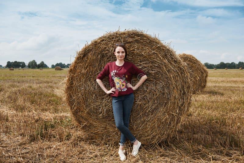 Młoda dziewczyna ma zabawę w polu, skoszony siano zawijający w haystack zdjęcia stock