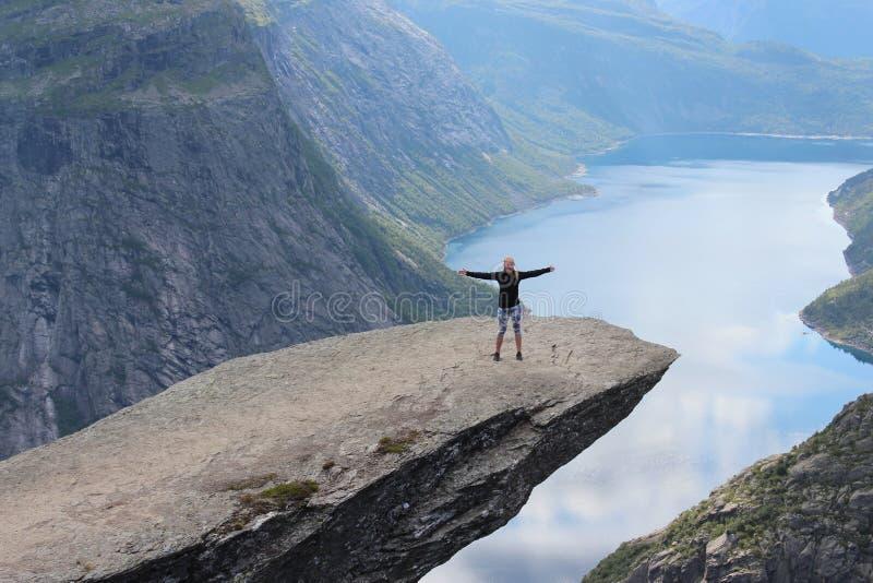 Młoda dziewczyna na błyszczka jęzorze (norw Trolltunga) zdjęcie royalty free