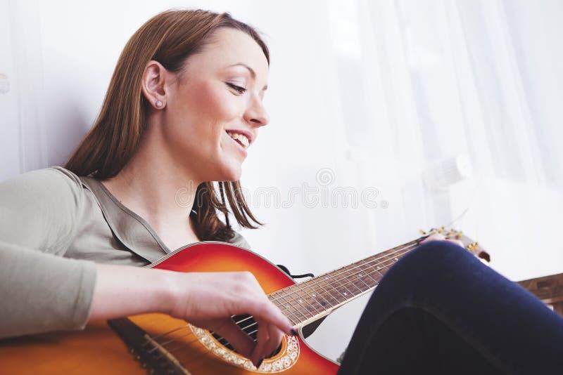 Młoda dziewczyna na kanapie bawić się gitarę fotografia royalty free