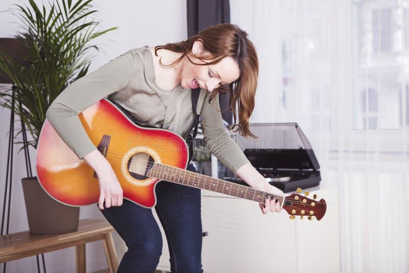 Młoda dziewczyna na kanapie bawić się gitarę zdjęcia stock