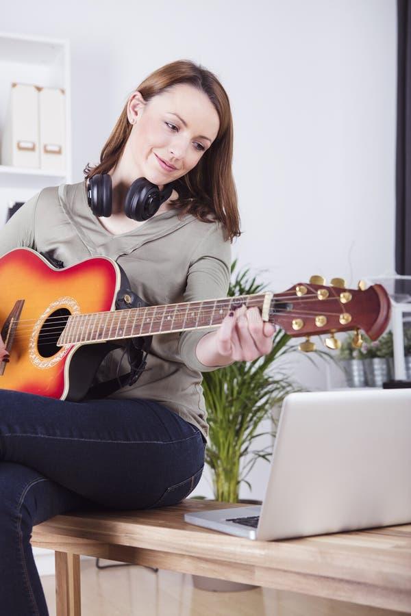 Młoda dziewczyna na kanapie bawić się gitarę zdjęcie stock
