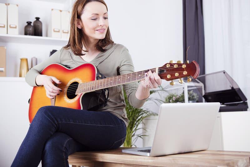Młoda dziewczyna na kanapie bawić się gitarę obrazy stock