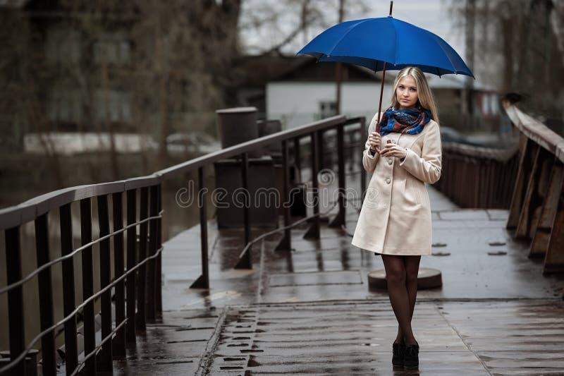 Młoda dziewczyna na moscie na chmurnym deszczowym dniu zdjęcie stock