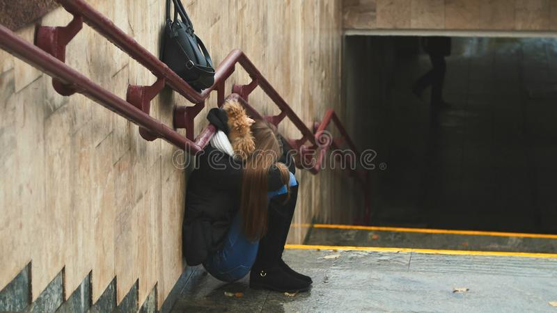 Młoda dziewczyna na schodkach w metro deprymujący siedzący samotnym zaciemnia twarz z jego handsand płaczem Jesień obraz royalty free