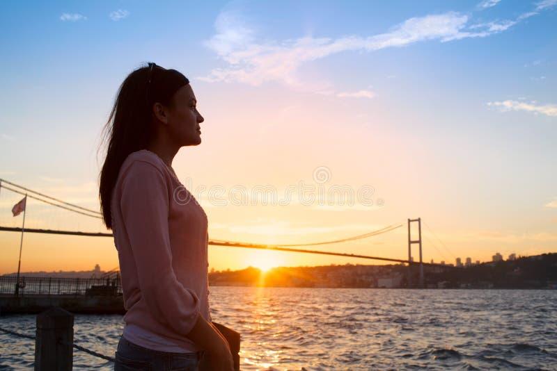 Młoda dziewczyna na tle Bosphorus zmierzch i most zdjęcie stock