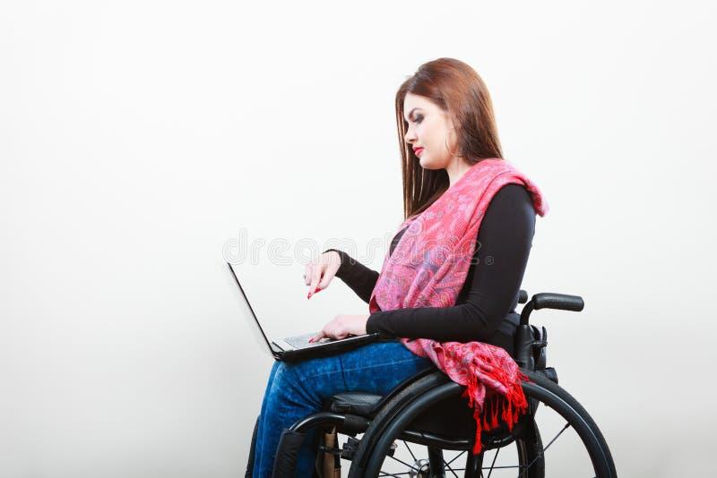 Młoda dziewczyna na wózka inwalidzkiego surfingu sieci obraz royalty free