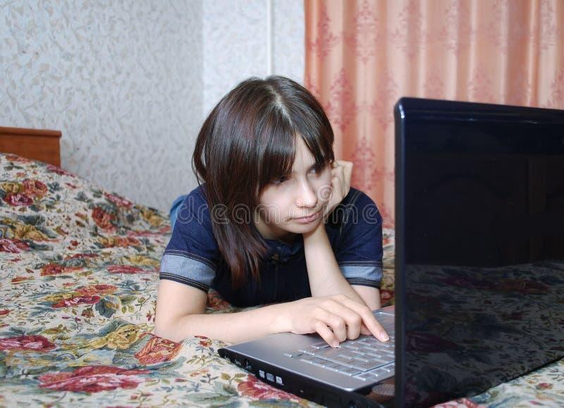 Młoda dziewczyna nastolatek kłama na łóżku z laptopem Patrzeje dla informacji o internecie obrazy royalty free