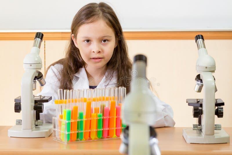 Młoda dziewczyna naukowiec z mikroskopem i próbnymi tubkami w nauce l obrazy stock
