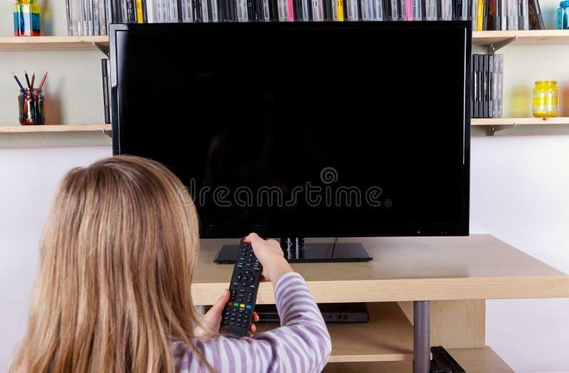 Młoda dziewczyna obraca dalej lub z TV z pilot do tv obrazy stock
