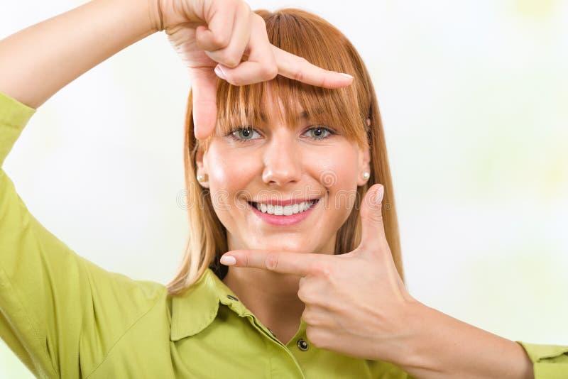 Młoda dziewczyna obramia jej twarz z rękami obrazy stock