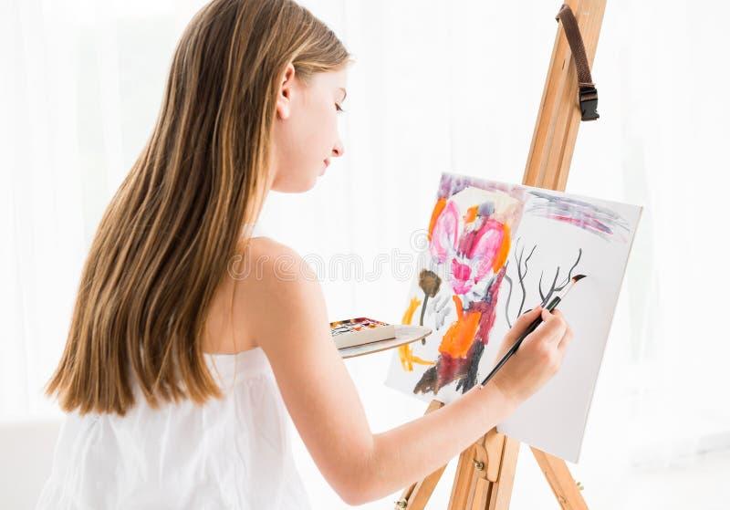 Młoda dziewczyna obraz na canva w sztuki studiu zdjęcia stock