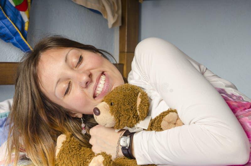 Młoda dziewczyna ono uśmiecha się podczas gdy ściskający jej niedźwiedzia obrazy stock