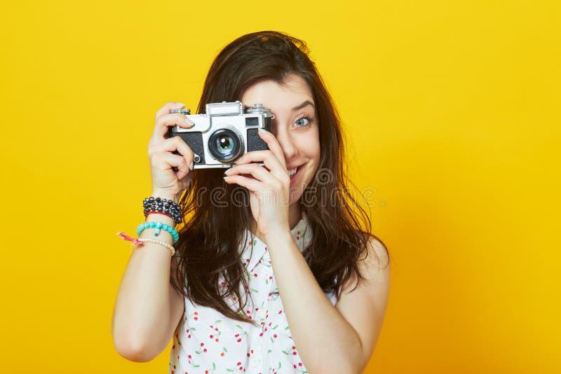 Młoda dziewczyna ono uśmiecha się przeciw żółtej ścianie z retro kamerą zdjęcia royalty free