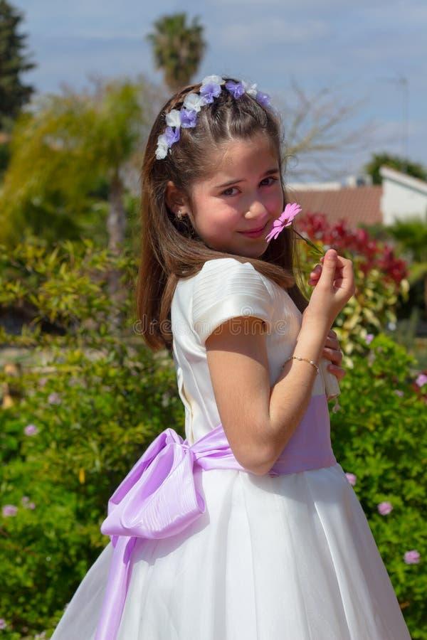 Młoda dziewczyna ono uśmiecha się z kwiatem zdjęcia stock