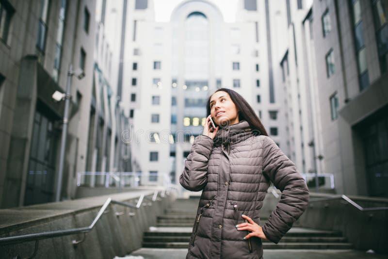 Młoda dziewczyna opowiada na telefonie komórkowym w podwórzowym centrum biznesu dziewczyna z długim ciemnym włosy ubierał w zimy  zdjęcia stock