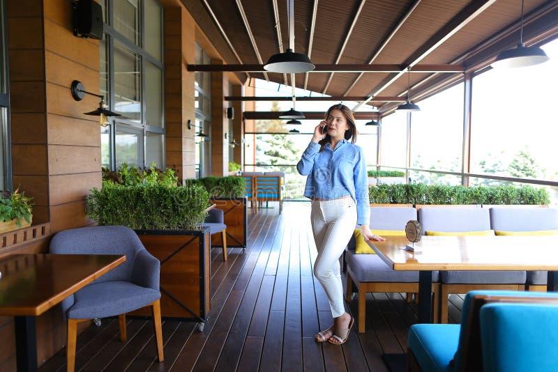 Młoda dziewczyna opowiada smartphone przy restauracją obrazy royalty free