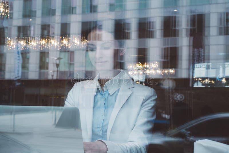 Młoda dziewczyna patrzeje laptopu działania i monitoru w białym biznesie odziewa za szklanym okno w kawiarni z bokeh głównymi atr obraz royalty free