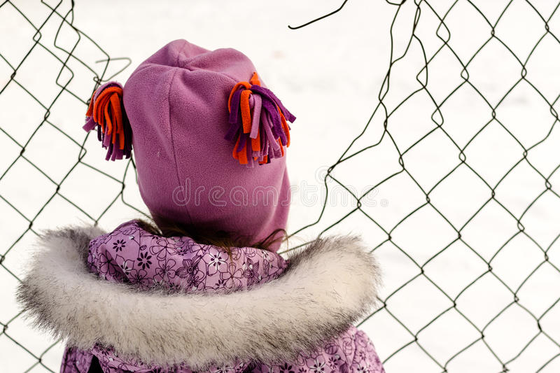 Młoda Dziewczyna Patrzeje Przez Łamanego Łańcuszkowego połączenia ogrodzenia zdjęcia stock