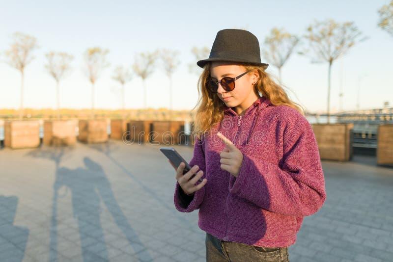 Młoda dziewczyna patrzeje w telefonie komórkowym i pokazuje palec wskazującego w górę obrazy royalty free