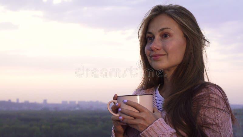 Młoda dziewczyna pije ciepłego napój i cieszy się zmierzch zdjęcia stock