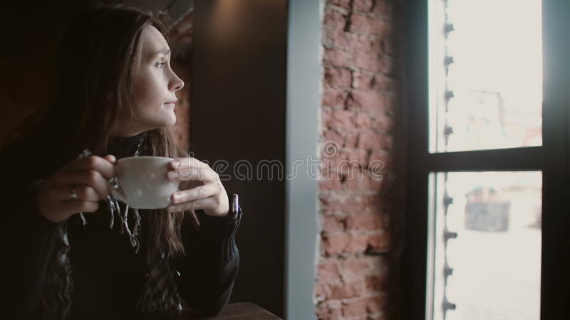Młoda dziewczyna pije herbaty od kubka out i przyglądający nadokienny obsiadanie w nowożytnym loft łomota 4k zdjęcie stock