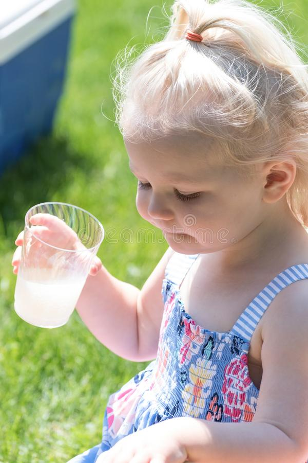 Młoda dziewczyna pije lemoniadę outside na gorącym letnim dniu fotografia stock