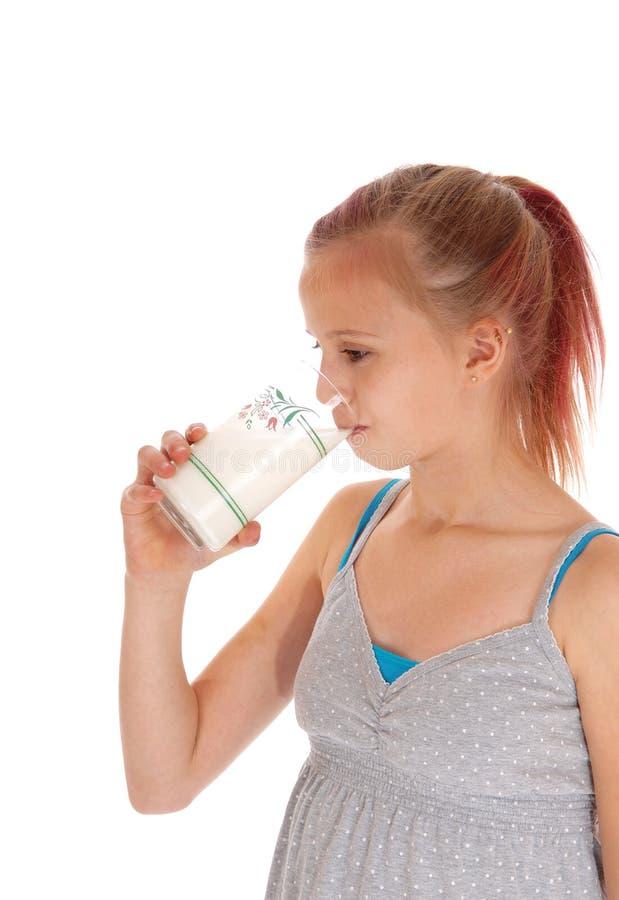 Młoda dziewczyna pije szkło mleko zdjęcia stock