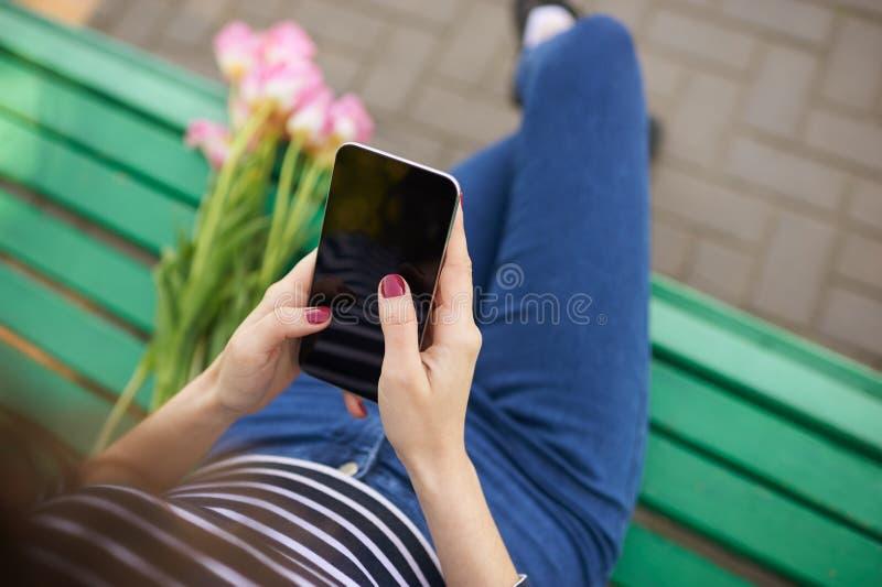 Młoda dziewczyna pisać na maszynie na ekranie jej telefon komórkowy zdjęcie royalty free