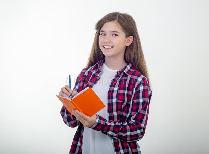 Młoda dziewczyna pisze w notatnika używać ołówkowy i uśmiechnięty Uczeń, na bielu obraz royalty free