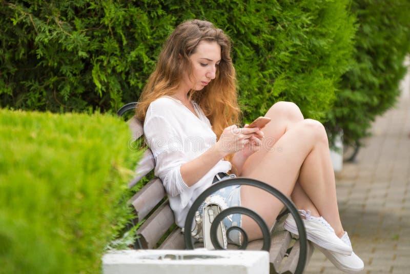 Młoda dziewczyna pisze wiadomości na telefonie, na parkowej ławce fotografia stock