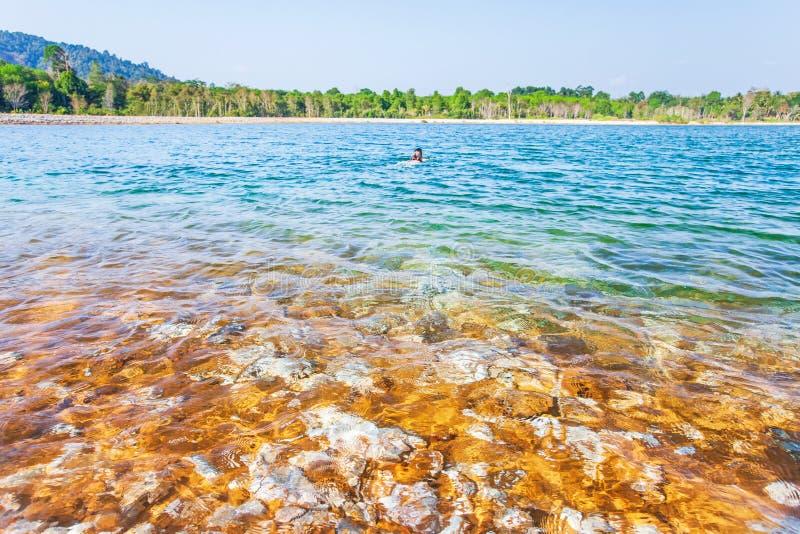 Młoda dziewczyna podróżnik relaksuje w turkusowej świeżej wodzie tropikalny jezioro, zamazujący bławy i - nieba tło zdjęcie royalty free