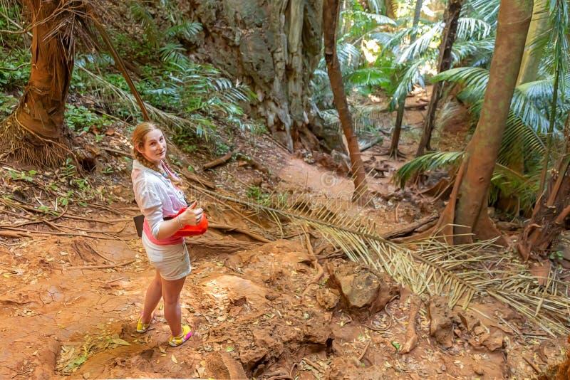 Młoda dziewczyna podróżnik w biel stojakach w tropikalnej dżungli i iść iść dalej Wokoło gąszczy i drzewek palmowych, średniogórz fotografia royalty free
