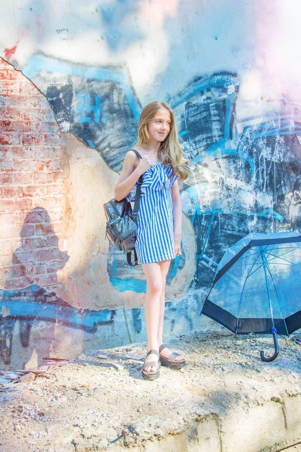 Młoda dziewczyna pozuje przeciw ścianie z graffiti słońce, cajgów stojaki przy malować ścianami obraz stock