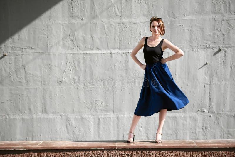 Młoda dziewczyna pozuje przeciw betonowej ścianie, ubierającej w czerni, ciężkim świetle i cieniach, zdjęcia royalty free