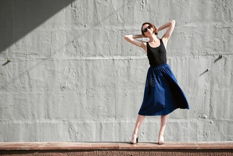 Młoda dziewczyna pozuje przeciw betonowej ścianie, ubierającej w czerni, ciężkim świetle i cieniach, zdjęcie stock